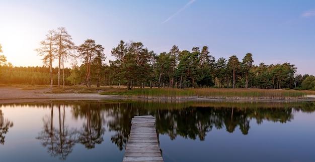 Bela paisagem do lago ao pôr do sol colorido com uma passarela. árvores refletindo na água