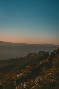 Bela paisagem do pôr do sol sobre uma paisagem verde com montanhas rochosas