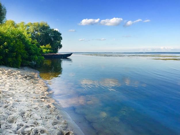 Bela paisagem do reservatório de kaniv com um barco perto da costa, ucrânia