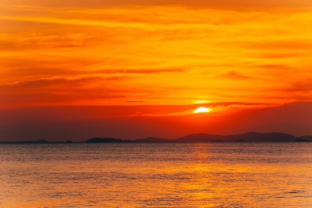 Bela paisagem do sol ardente e céu laranja acima dele