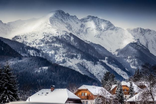 Bela paisagem dos altos alpes austríacos com casas tradicionais cobertas de neve