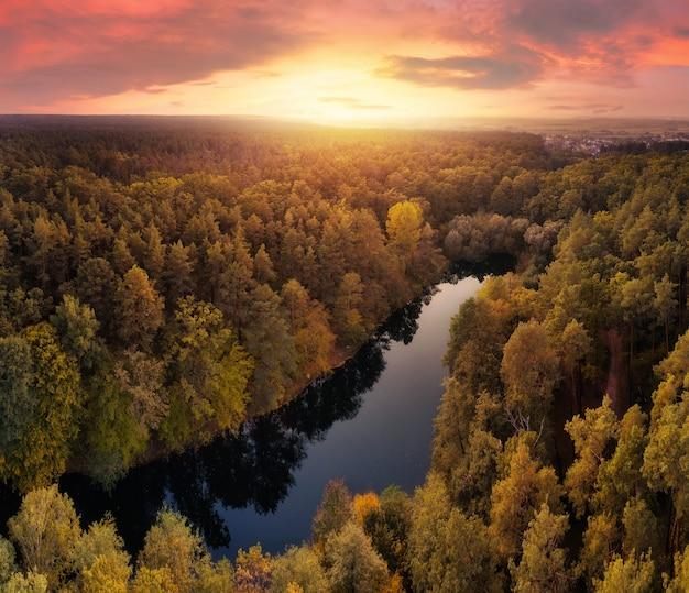Bela paisagem dramática do lago na floresta de outono no céu do pôr do sol