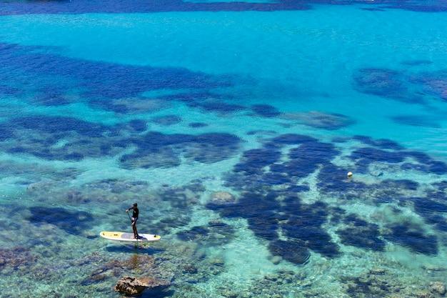 Bela paisagem em ibiza do oceano azul em um dia ensolarado com um homem praticando paddle surf. conceito de verão e férias.