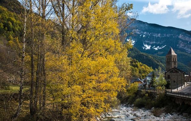 Bela paisagem em uma vila dos pirineus com montanhas nevadas, várias árvores, um rio e uma igreja