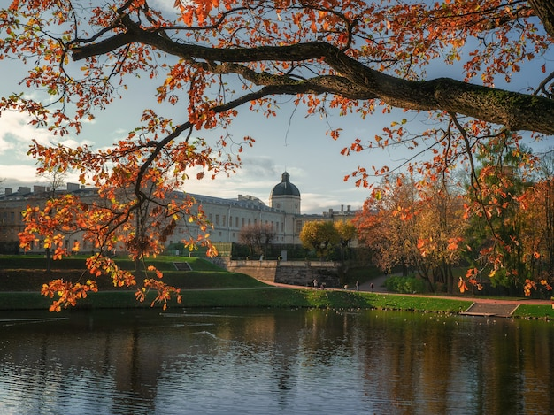 Bela paisagem ensolarada de outono do parque com um lago e um grande palácio gatchina. rússia.