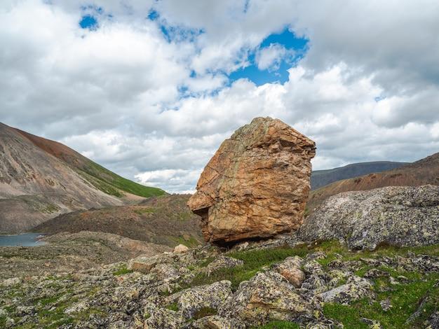 Bela paisagem montanhosa com pedra de granito gigante entre colina e montanhas. cenário colorido das terras altas com grande rocha entre a vegetação verde e as montanhas.