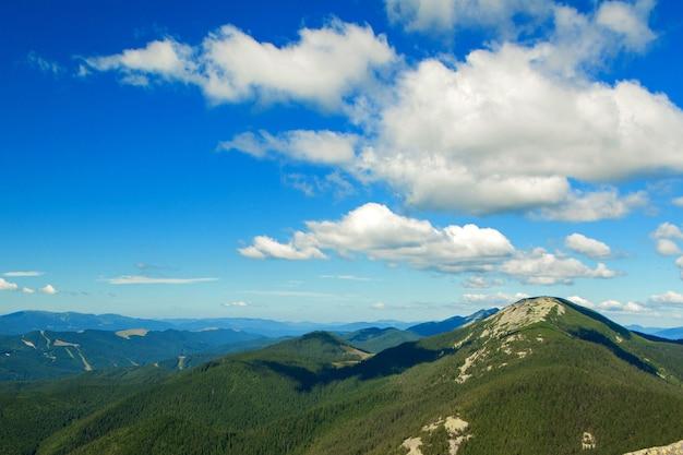 Bela paisagem montanhosa com picos cobertos de floresta e um céu nublado