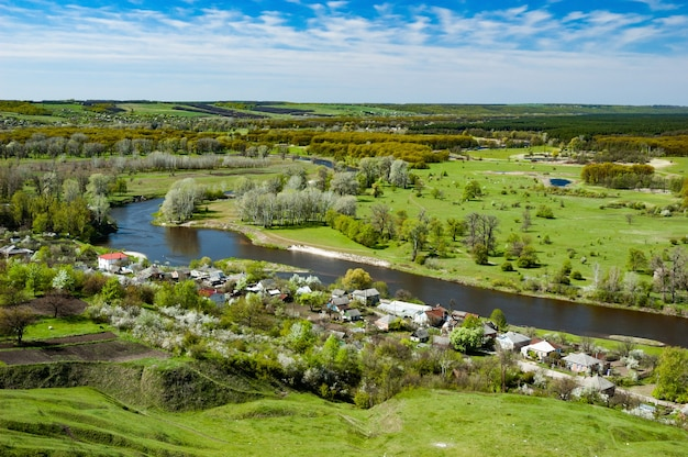 Bela paisagem natural de uma vila construída ao redor de um rio em um dia quente ensolarado de outono contra um céu azul. conceito de vida no campo. copyspace