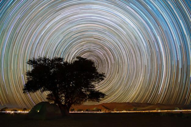 Bela paisagem noturna trilhas de estrelas na floresta de árvores quiver em keetmanshoop, namíbia