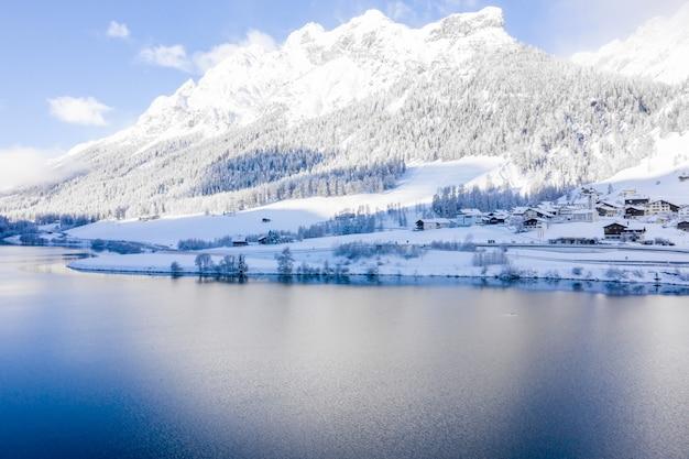 Bela paisagem panorâmica de um lago e montanhas cobertas de neve em um dia ensolarado