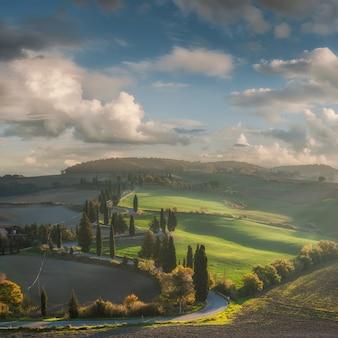 Bela paisagem rural com ciprestes e colinas, fazendas