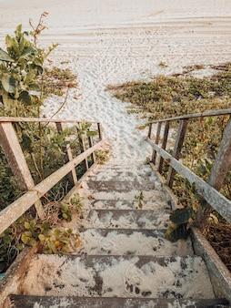 Bela paisagem tomada da escada para a praia com as cores douradas do pôr do sol