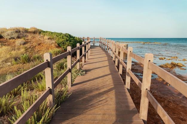 Bela paisagem tranquila com píer de madeira coberto de grama, colina, mar calmo e céu azul