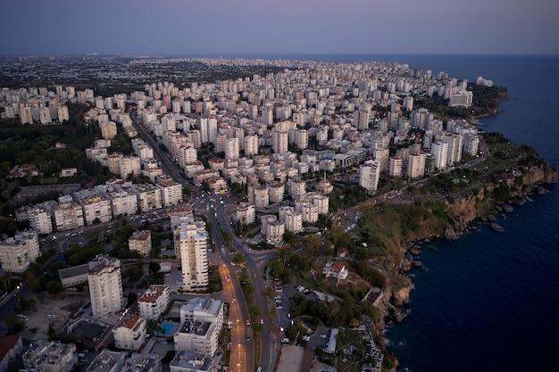 Bela paisagem urbana da cidade turca. pôr do sol de verão acima dos edifícios da cidade e do mar. viagem para a turquia.