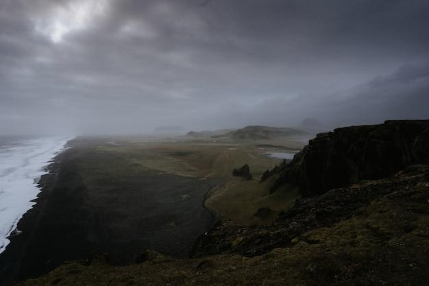 Bela paisagem verde com um lago cercado por altas montanhas envolto em névoa