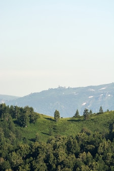 Bela paisagem verde montanha com grandes colinas e montanhas de neve com pedras grandes