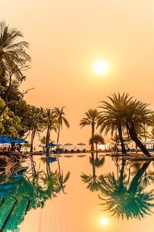 Bela palmeira com cadeira de guarda-chuva piscina em hotel resort de luxo na hora do nascer do sol - conceito de férias e férias