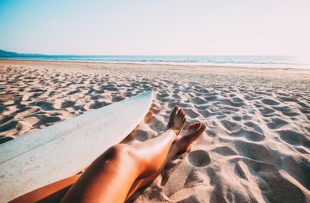 Bela perna de mulher sexy surfista tomando sol com prancha de surf na praia ao pôr do sol