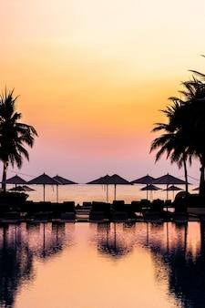 Bela piscina ao ar livre com cadeira de guarda-chuva silhueta ao redor no resort no tempo do nascer do sol