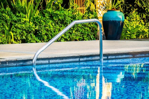 Bela piscina ao ar livre com cama espreguiçadeira e guarda-chuva no resort para viagens e férias