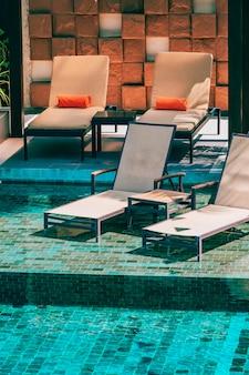 Bela piscina ao ar livre no hotel e resort com cadeira e deck para férias de lazer