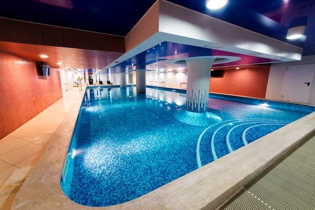Bela piscina azul com lugares para descansar.