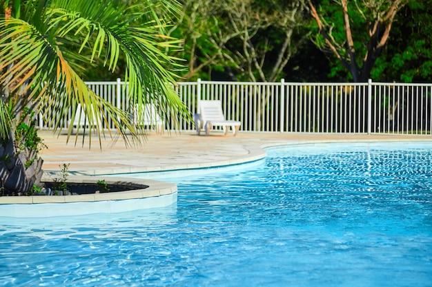 Bela piscina com água azul clara em dia ensolarado de verão