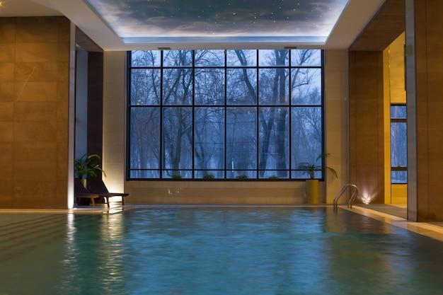 Bela piscina com janelas panorâmicas na noite de inverno