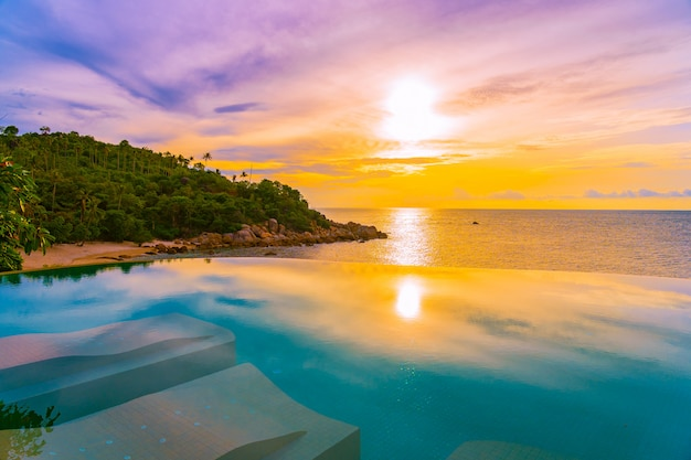Bela piscina de beiral infinito ao ar livre com palmeira de coco em torno do oceano do mar praia no nascer do sol ou por do sol