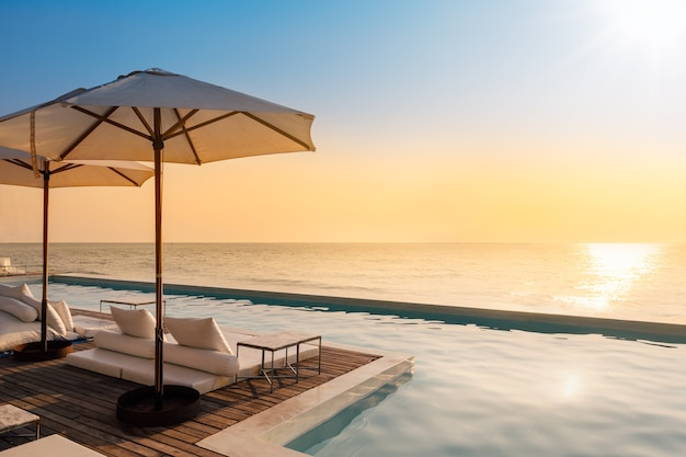 Bela piscina de luxo na vista para o mar e guarda-chuva e cadeira no resort do hotel