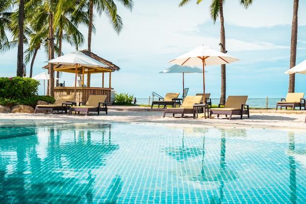 Bela piscina tropical com guarda-sóis e cadeiras