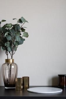 Bela planta artificial em vaso de vidro com borda de ouro inoxidável e configuração de vaso de ouro na mesa de madeira preta