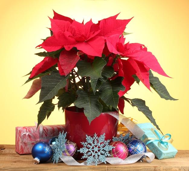 Bela poinsétia com bolas de natal e presentes na mesa de madeira