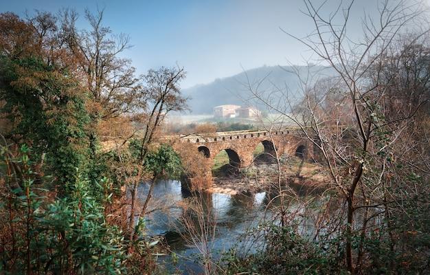 Bela ponte romana mística com névoa no outono