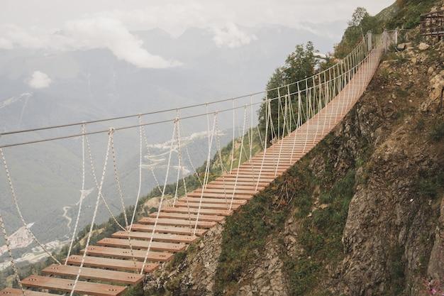 Bela ponte suspensa nas montanhas, uma força excitante de edifícios da natureza humana entre as ...