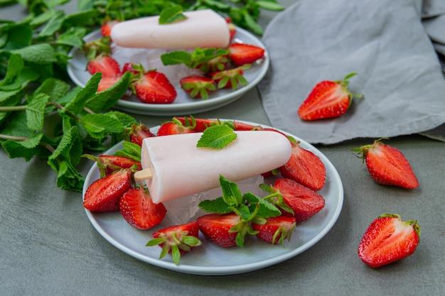 Bela porção de sorvete de frutas com morangos e gelo decorado com hortelã. colheres de sorvete de baunilha com frutas frescas.