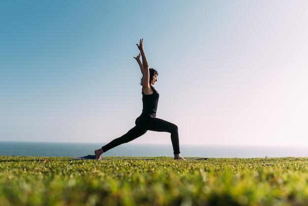 Bela postura de uma mulher praticando ioga ao ar livre. copie o espaço