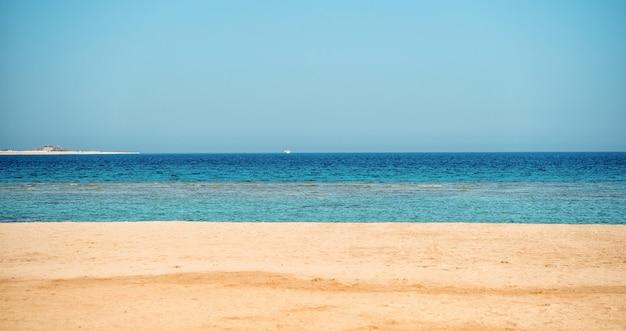 Bela praia com areia, céu azul, mar, água do oceano com barco no horizonte ensolarado verão ao ar livre como plano de fundo natural