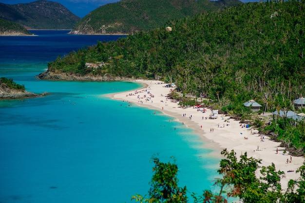 Bela praia com muitas pessoas e primeiro plano de colinas verdes, ilhas virgens de st. john nos.