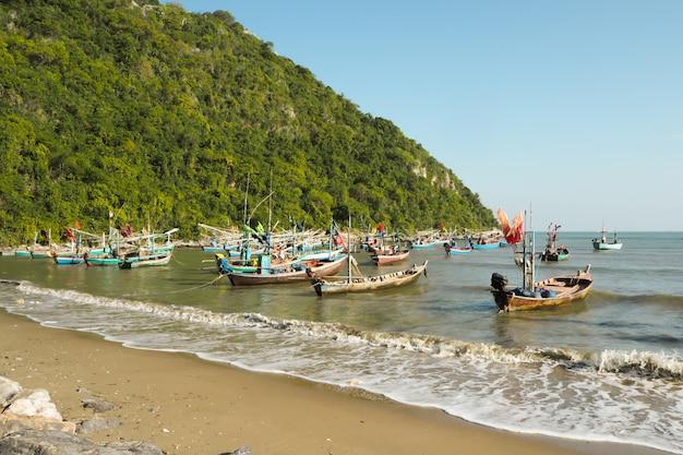 Bela praia com pedras e barcos de mar azul do pescador