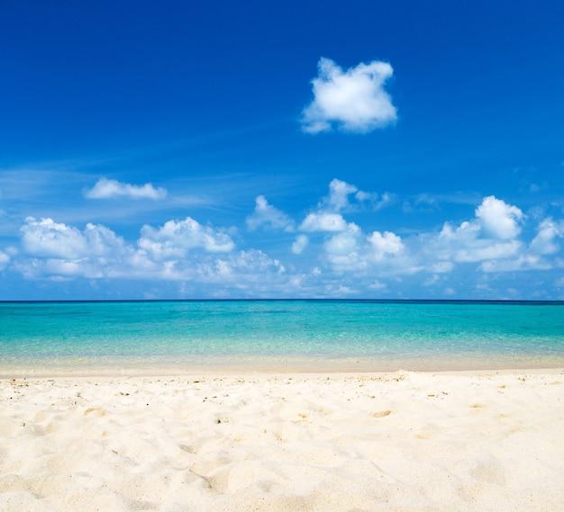 Bela praia de areia branca. mar tropical com céu azul nublado. paisagem de praia incrível