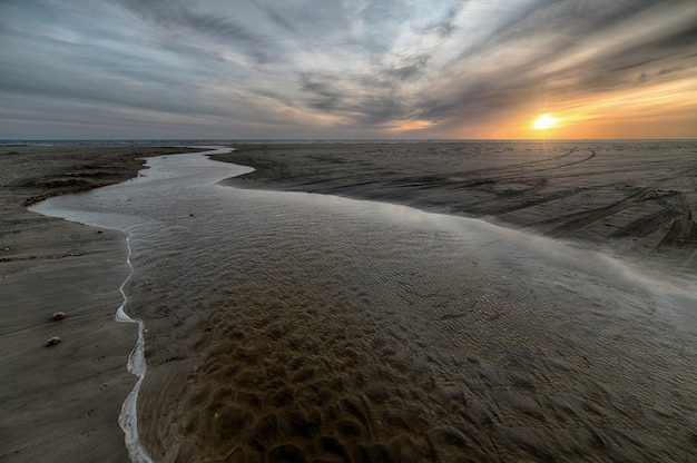 Bela praia de areia com mar durante a maré baixa