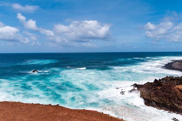 Bela praia na ilha de lanzarote. praia rodeada por montanhas vulcânicas / oceano atlântico e praia maravilhosa. lanzarote. ilhas canárias