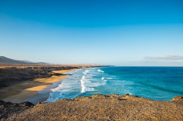 Bela praia selvagem com ondas e céu azuis do oceano - turismo de verão, lugar cênico de férias - céu azul e água - ponto de vista do penhasco e cenário litoral e costa
