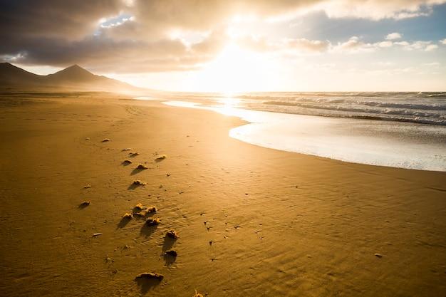 Bela praia sem ninguém para um destino cênico tropical - férias de verão - belo pôr do sol na costa com montanhas e ondas