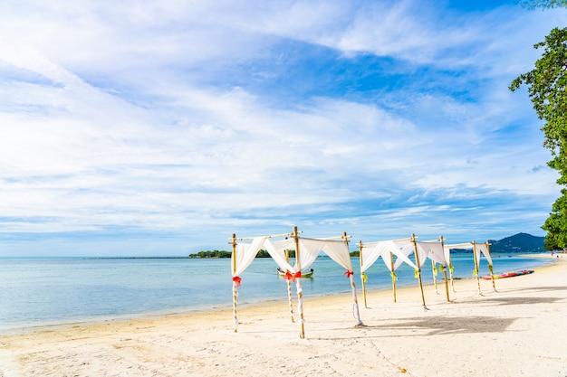Bela praia tropical ao ar livre oceano mar com guarda-chuva e lounge deck