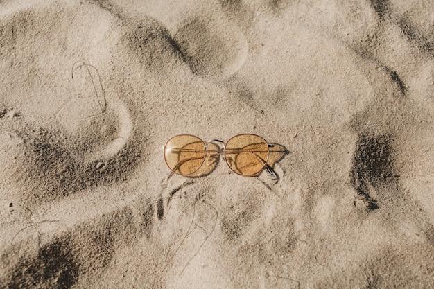 Bela praia tropical com areia branca, degraus e óculos de sol amarelos ensolarados Foto Premium
