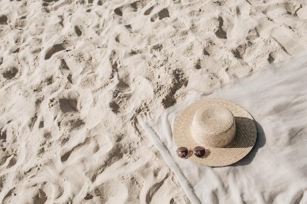 Bela praia tropical com areia branca, degraus, manta neutra com chapéu de palha e óculos escuros Foto Premium