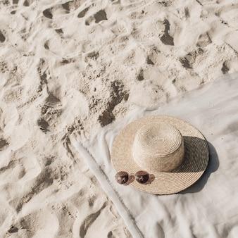 Bela praia tropical com areia branca, degraus, manta neutra com chapéu de palha e óculos escuros