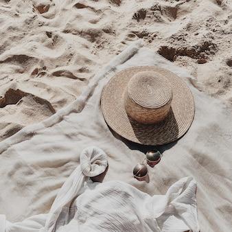 Bela praia tropical com areia branca, degraus, manta neutra com chapéu de palha, óculos escuros e camisa branca